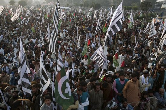 The black-and-white banner of the Jamaat-ud-Dawa, the front group for the Lashkar-e-Taiba, is prevalent at an anti-US rally in Lahore in December 2011. AP photo.